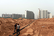 A small construction crew lays water pipes in the middle of the desert leading towards a new apartment development on the outskirts of Yulin, Shaanxi Province, China on 14 August, 2011. Like many coal rich regions in China's arid northwest, a vast amount of mineral wealth has been re-invested into the local economy in the form of speculative real estate ventures, creating hundreds of new cities that claims few real residents.