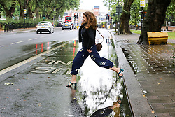 © Licensed to London News Pictures. 27/07/2019. London, UK. Helen Waddell jumps over a flood on Green Lanes in north London, caused by heavy overnight downpour. Photo credit: Dinendra Haria/LNP