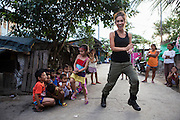 Myleene Klass, a high profile UK celebrity, TV host, violinist and pianist, dances in the streets with children in an urban slum where she had visited an under-privileged mother and her family in Paranaque, Metro Manila, The Philippines on 19 January 2013. Photo by Suzanne Lee for Save the Children UK