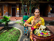 """08 AUGUST 2017 - UBUD, BALI, INDONESIA: A woman prays and in a family compound during a ceremony to honor a family temple in Ubud, Bali. Balinese Hindus have a 210 day calender and every almost every family compound on Bali has a family temple. Once a year (or every 210 days) families celebrate the """"birthday"""" of their temple with a ceremony.     PHOTO BY JACK KURTZ"""