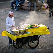 A street vendor grills fresh fish on a cart at Karakoy Fish Market in Istanbul near the Galata Bridge.