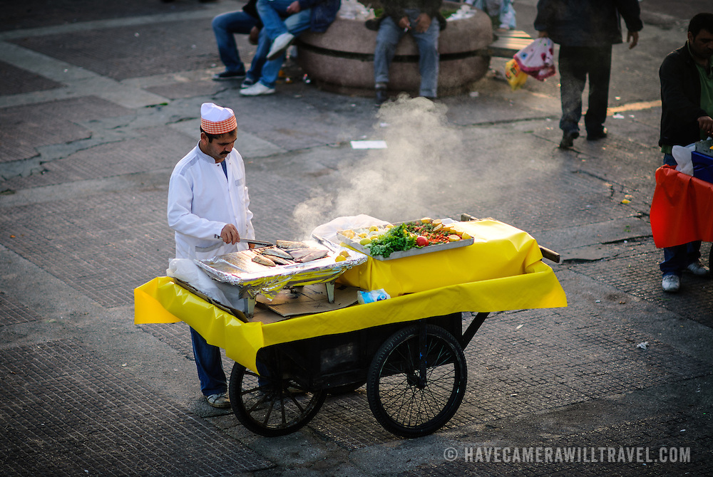 A street vendor grills fresh fish on a cart at Karakoy Fish Market in Istanbul near the Galata Bridge.