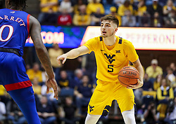 Feb 12, 2020; Morgantown, West Virginia, USA; West Virginia Mountaineers guard Jordan McCabe (5) calls out a play while guarded by Kansas Jayhawks guard Marcus Garrett (0) during the second half at WVU Coliseum. Mandatory Credit: Ben Queen-USA TODAY Sports