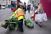 Youngwoman laden with shopping bags including Primark bags passes a street cleaner attending to rubbish bins as the national lockdown ends and the new three tier system of local coronavirus restrictions begins, shoppers head out to Oxford Street to catch up on shopping as non-essential shops are allowed to reopen on 2nd December 2020 in London, United Kingdom. Many shoppers wear face masks outside on the street as a precaution as there are so many people around.