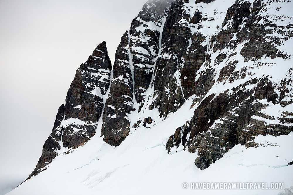"""Steep cliffs and jagged rocks lining the edges of the Lemaire Channel on the western coast of the Antarctic Peninsula. The Lemaire Channel is sometimes referred to as """"Kodak Gap"""" in a nod to its famously scenic views."""