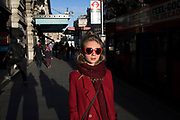 Evening light illuminating a young woman wearing heart shaped red sunglasses and a red coat walking along Piccadilly in London, England, United Kingdom.