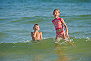 Two kids play in ocean waves.