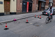 A cyclist wearing pink gloves rides past a split pink plastic sphere which has come to rest in the gutter on a side street in central London, on 23rd February 2021, in London, England.