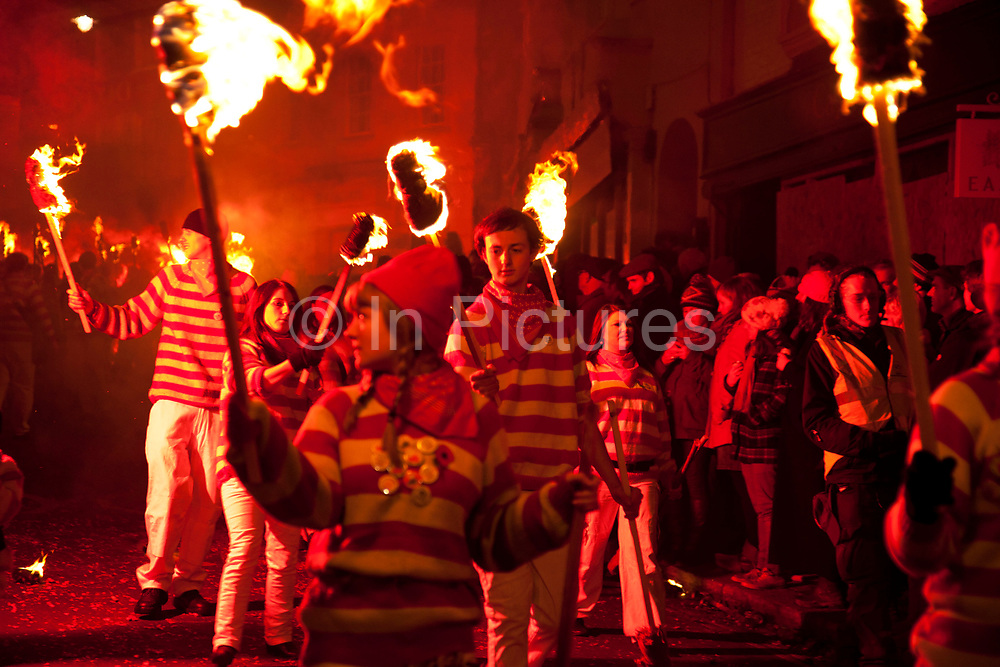 Lewes, UK. Monday 5th November 2012. Members of Waterloo bonfire society carry burning torches on Bonfire Night celebration in the town of Lewes, East Sussex, UK which form the largest and most famous Guy Fawkes Night festivities. Held on 5 November, the event not only marks the date of the uncovering of the Gunpowder Treason and Plot in 1605, but also commemorates the memory of the 17 Protestant martyrs from the town burnt at the stake for their faith during the Marian Persecutions of 1555–57. There are six bonfire societies putting on parades involving some 3,000 people.