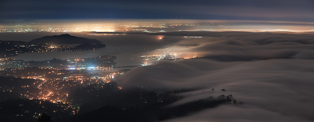 Coastal fog over the Marin Headlands descends into Sausalito, Mill Valley and Larkspur as the cities of San Francisco Bay shine in background. As seen from the Summit of Mount Tamalpais. Marin County, CA.
