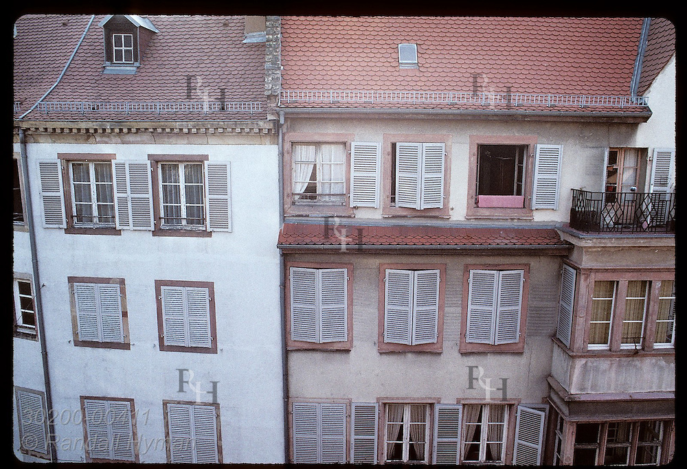 Fifth-story view of quaint shuttered windows and building facades on street in central Strasbourg. France