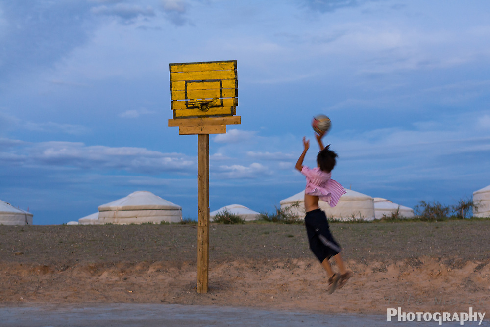 MONGOLIA, GOBI DESERT: boy playing basketball in desert with a makeshift court and  ger huts in background