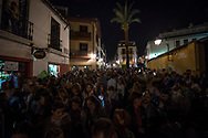A large crowd waiting for a procession in Cordoba, a woman is lit by her smartphone screen. Andalusia, Spain