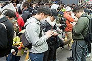 crowd of peeple all looking at there mobile phone Japan Tokyo