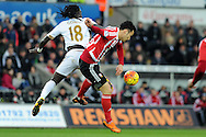 Swansea's Bafetimbi Gomis (18) and Southampton's Maya Yoshida challenge for a header. Barclays Premier league match, Swansea city v Southampton at the Liberty Stadium in Swansea, South Wales on Saturday 13th February 2016.<br /> pic by  Carl Robertson, Andrew Orchard sports photography.