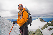 Yoav Bar-Ness contemplates the climbing route to the summit of Mount Shuksan from the rim of the Sulpide Glacier, North Cascades National Park, Washington.