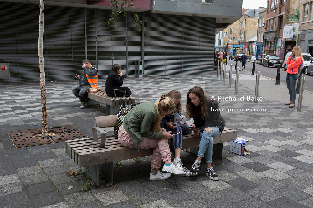 Young women look at a mobile phone in a street near Brick Lane, on 29th August 2018, in London, England.