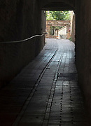 A dark alley/tunnel in San Gimignano, Italy leads visitors along a cobblestone walkway to a courtyard contiaining sculpture