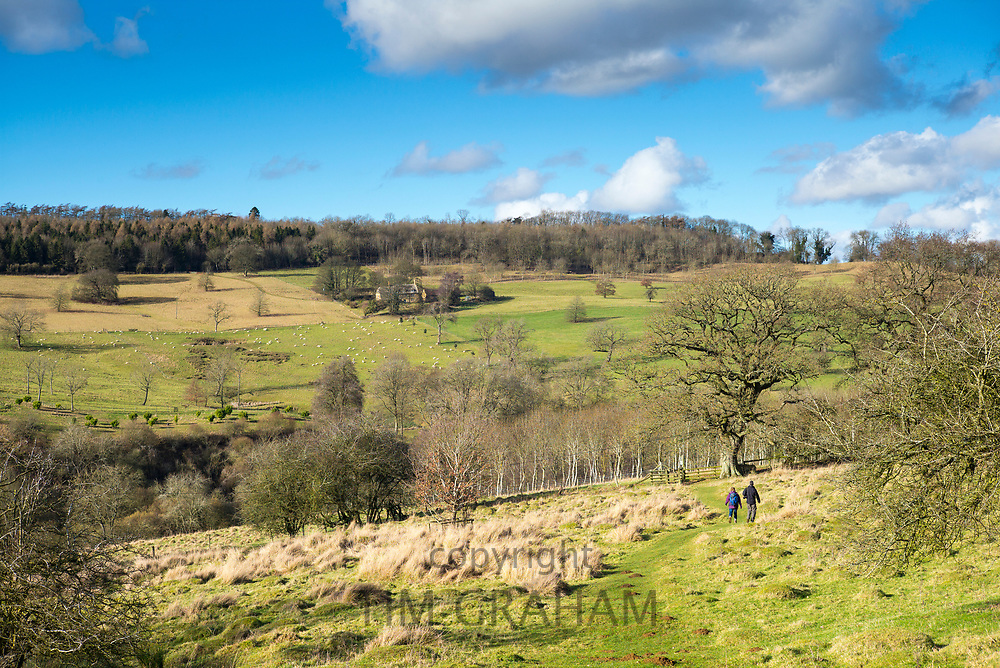 Walkers strolling on country walk through farmland by Snowshill in The Cotswolds, England