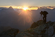Photographer on the rocks and the sunset with the peaks of Piz Platta and Piz Forbesch, Julier, Parc Ela, Grisons, Switzerland