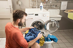 Man sitting in front of washing machine with clothes in laundry basket