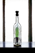 empty transparent wine bottle with a halve full green bottle behind it