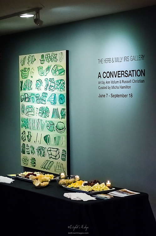 A piece of artwork, a table of Hors d'Oeuvres, and relevant information on the wall during a gallery display of two artists' works.