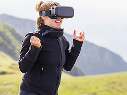 Woman wearing virtual reality glasses on mountain