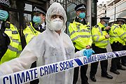 Extinction Rebellion 'crime scene investigators' in white suits and masks put up climate crime scene tape to investigate areas of ecocide in a performance outside the Brazilian Embassy on 7th September 2020 in London, United Kingdom. The 20 investigators were protesting at the Brazilian government's alleged involvement in ecocide in the Amazon. Extinction Rebellion is a climate change group started in 2018 and has gained a huge following of people committed to peaceful protests. These protests are highlighting that the government is not doing enough to avoid catastrophic climate change and to demand the government take radical action to save the planet.