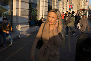 A stylish young woman walks and talks into her phone on Piccadilly, on 21st January 2020, in London, England.
