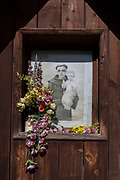 Fading flowers and a portrait of Saint Antoni Padewski - a Polish village shrine, on 20th September 2019, in jaworki, near Szczawnica, Malopolska, Poland.