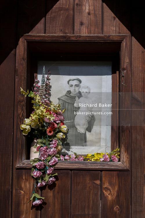 Fading flowers and a portrait of Saint Antoni Padewski - a Polish village shrine, on 20th September 2019, in jaworki, near Szczawnica, Malopolska, Poland.