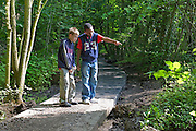 2 boys on path in wood looking at wildlife and nature