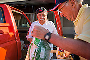 05 NOVEMBER 2013 - PHOENIX, AZ: ALAN GELLER, right, a volunteer, helps JUAN ARMEDARIZ, left, put food into his truck at St. Mary's Food Bank in Phoenix, AZ. Demand at St. Mary's has continued to increase even as government assistance is reduced. Over the summer, St. Mary's Phoenix location provided emergency food for 300 - 400 families per day. They are currently supporting about 600 families per day. Part of the increase is seasonal but a large part of it is no clients coming to the food bank for the first time. More than 1.1 million Arizonans who use the Supplemental Nutrition Assistance Program, known as food stamps, saw their benefits reduced Friday, Nov. 1, in a long-planned national cut that was tied to the economic stimulus which was a part of the American Recovery and Reinvestment Act. The cuts imposed last week range from $11 a month for a single recipient to $65 or more for large families. Many of SNAP receipients already use food banks to supplement their government assistance and the cuts in the SNAP program are expected to increase demand even more.   PHOTO BY JACK KURTZ