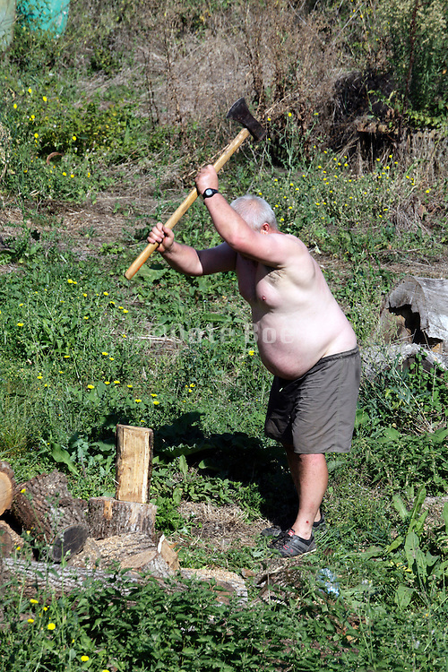 obese man busy with wood chopping