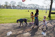 On the first day of the Easter Bank Holiday weekend, and at the end of the second week of lockdown restrictions by the UK government, a family use their daily exercise entitlement to spend a warm afternoon near a stencil for keeping 2 metres apart in Ruskin Park in a public green space in the borough of Lambeth, on 10th April 2020, in London, England.