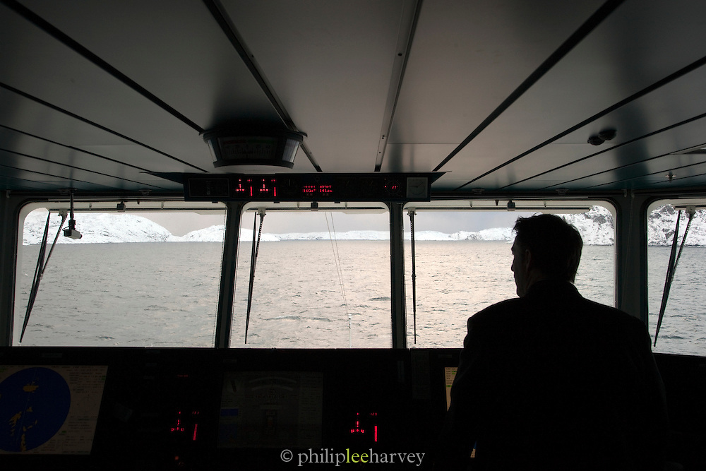 A crew member on the bridge pilots a large cruise ship in the waters of Finnmark region, northern Norway