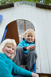 Two young kids playing in garden summerhouse