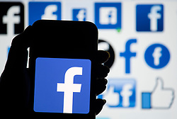 File photo dated 25/3/2018 of the logo of Facebook displayed on a smartphone, as researchers are developing a device to allow users to feel Facebook messages through their skin.