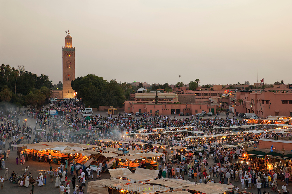 The minaret of the Koutoubia Mosque, towering over hundreds of people walking between food stalls, in the Djemaa el Fna in the medina of Marrakech, Morocco. Every night the main square fills with dozens of food vendors and their carts.