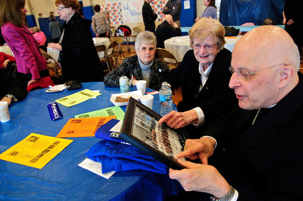 Chicago Archbishop Francis Cardinal George (R to L) reviews his 1951 class photo with fellow alumni Sr. Frances Ryan and Mary Ann Rosso Ulm during a reunion in the gymnasium of their alma matter, St. Pascal Catholic Parish. George graduated with the class of 1951 and was ordained a priest there in 1963. March 4, 2012 l Brian J. Morowczynski~ViaPhotos..For use in a single edition of Catholic New World Publications, Archdiocese of Chicago. Further use and/or distribution may be negotiated separately. ..Contact ViaPhotos at 708-602-0449 or email brian@viaphotos.com.
