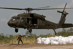 12 june 2010. Wetlands of Plaquemines Parish, South Louisiana. <br /> An army helicopter on a sandbagging mission. Sand bags attempt to join the dots and connect what little remains of fragile barrier islands. It is unlikely the bags will survive a hurricane. Where once there was land, there is only the mere outline of old canals and channels, many dug by oil companies to pump their product ashore with little regard to the effects the chopping up of the wetlands would have. Chronic erosion of the land, a football pitch every 50 minutes, greatly reduced protection from hurricanes and impending BP oil slicks is the direct result of mismanagement and utter disregard for the environment. The army corps of engineers and the oil companies, together with inept government have a great deal to answer for. <br /> View from a blackhawk helicopter flown by airmen of the Nebraska Air National Guard over southern Louisiana as they assist in the dumping of sand bags onto barrier islands in a vain attempt to prevent BP oil from getting into the inner  wetlands. As valiant as their efforts are, the dumping of sand bags may well prove to be a complete waste of manpower, resources and money. A hurricane will likely roll over and blast through any sandbag 'barrier island,' blowing thousands of large white plastic bags far and wide across the landscape. That will really help the environment! <br /> Meanwhile, the mighty Mississippi river runs straight out to sea nearby, her valuable land building sediment carried far out into deep ocean as the region struggles to find a way to reverse the disastrous effects of man's interference with her flow. <br /> Photo credit; Charlie Varley/varleypix.com