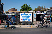 Two men cycle past a MOT testing garage offering free MOT's for all NHS (National Heath Service) staff on 23th April 2020 in London, United Kingdom.There have been almost 133,495 reported cases of the COVID-19 coronavirus in the United Kingdom and almost 19,000 deaths. The country is in its fifth week of lockdown measures aimed at slowing the spread of the virus.