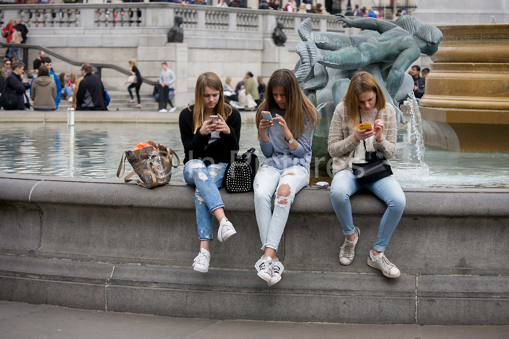 Three teenage girls are lost in the world of smartphone apps and messaging, in Trafalgar Square. While in a very busy environment, the capital's main square in central London, the teenagers obsessively tweet and message their friends at home, completely unaware of their surroundings, absorbed in the functions of their devices and their young lives. Sitting on the walls of the fountains, they are isolated from each other and the noise around them. In the backgrounds are tourists enjoying the architecture and ambience of a busy city.