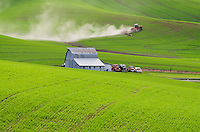 Farmer working the rolling hills of green wheat fields in the Palouse region of the Inland Empire of Washington