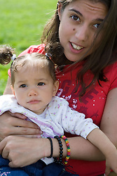 Young woman with Cerebral Palsy holding a baby in her arms,