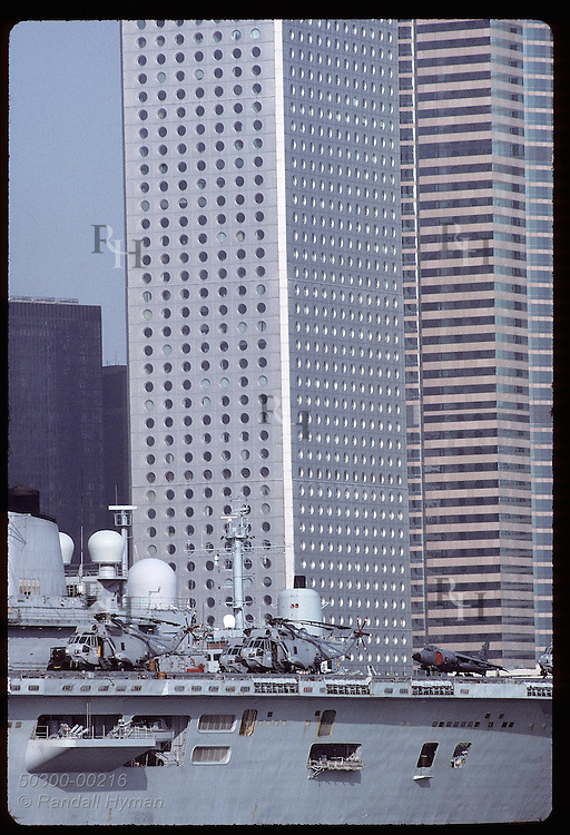 Jets & choppers on British warship contrast with Central District skyscrapers on a sunny day (v). Hong Kong
