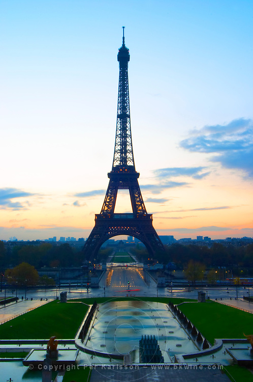 The Eiffel Tower in Paris in early morning dawn with the sun rising on the horizon, pale blue sky some white clouds and the sunlight golden yellow seen from the Place Trocadero square Paris France