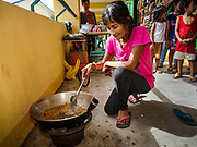 24 JANUARY 2018 - LIGAO, ALBAY, PHILIPPINES: WINEMINDA BON, an evacuee from a community near the Mayon volcano, fries banana blossoms in the hallway of the school she is temporarily living in in Ligao with 1,849 other people from the volcano. The Mayon volcano continued to erupt Tuesday night and Wednesday forcing the Albay provincial government to order more evacuations. By Wednesday evening (Philippine time) more than 60,000 people had been evacuated from communities around the volcano to shelters outside of the 8 kilometer danger zone. Additionally, ash falls continued to disrupt life beyond the danger zones. Several airports in the region, including the airport in Legazpi, the busiest airport in the region, are closed indefinitely because of the amount of ash the volcano has thrown into the air.    PHOTO BY JACK KURTZ