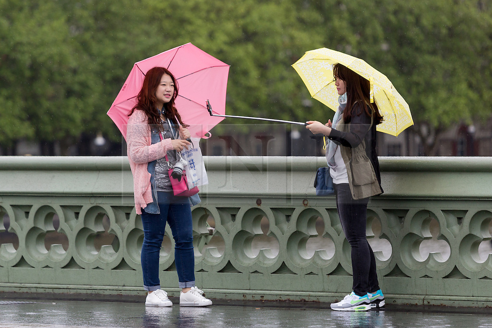 © Licensed to London News Pictures. 14/05/2015. London, UK. Two women with umbrellas try and take a selfie during heavy rain and wet and windy weather in Westminster, central London today. Photo credit : Vickie Flores/LNP
